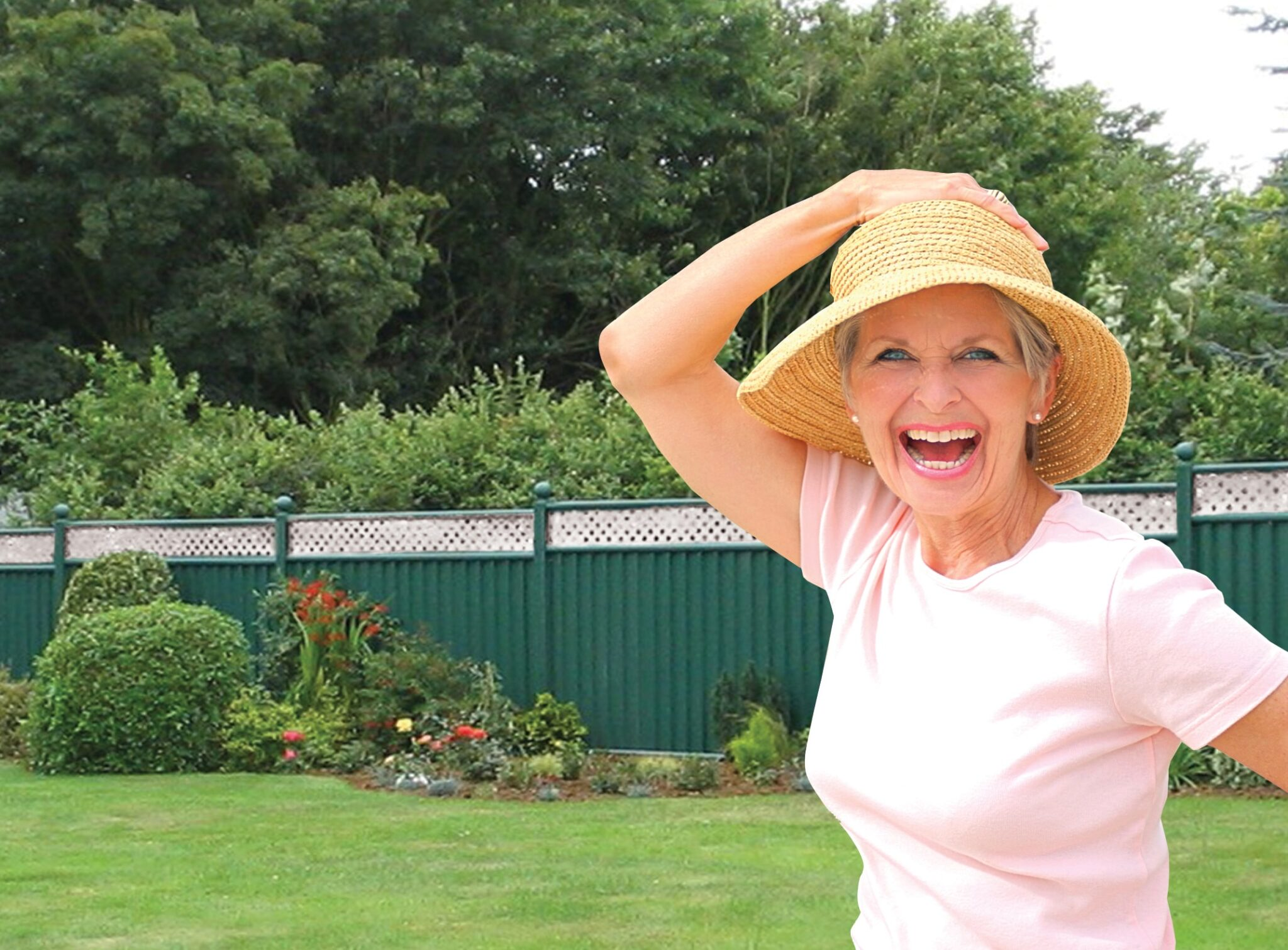 Happy Older Woman In Front of a Green Fence with Cream Trellis Top